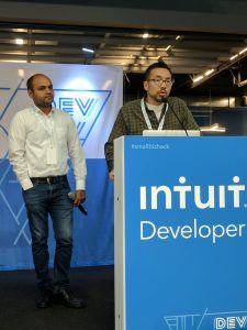 Jeff and Piyush presenting on stage at hackathon.