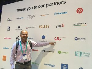 Dilli Labs founder Piyush Hari poses with Dilli Labs logo in background at Samsung Developer Conference 2019.